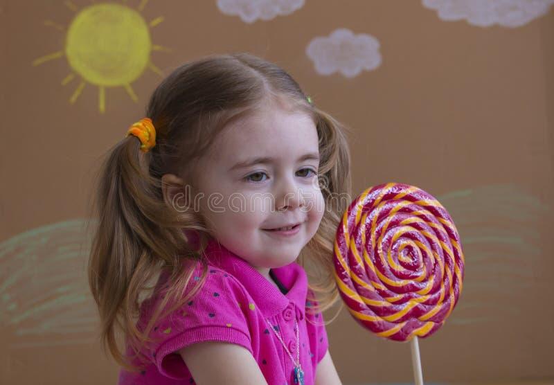 Śmieszny dziecko z cukierku lizakiem, szczęśliwa mała dziewczynka je dużego cukrowego lizaka, dzieciak je cukierki obrazy royalty free