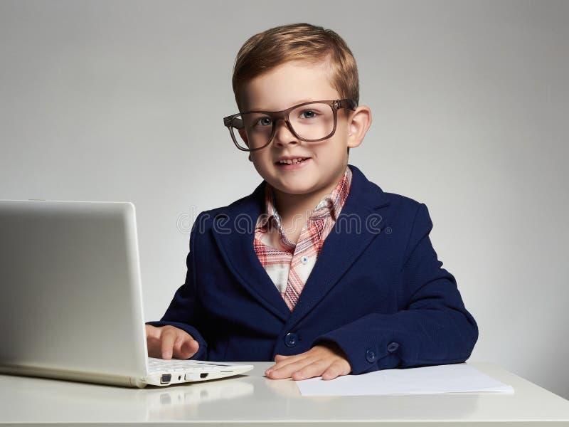 Śmieszny dziecko z komputerem Młoda biznesowa chłopiec obrazy stock
