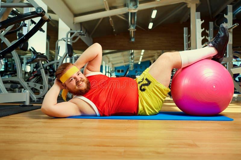 Śmieszny gruby mężczyzna robi ćwiczeniom na podłoga w gym zdjęcia stock