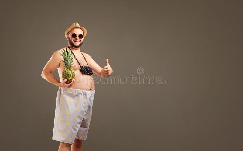 Śmieszny gruby mężczyzna w kapeluszu z ananasowy ono uśmiecha się w lecie fotografia stock