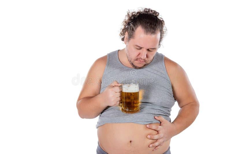 Śmieszny gruby mężczyzny uczucie szczęśliwy i zrelaksowany, mienia świeży zimny piwo w jego rękach na białym tle obraz stock