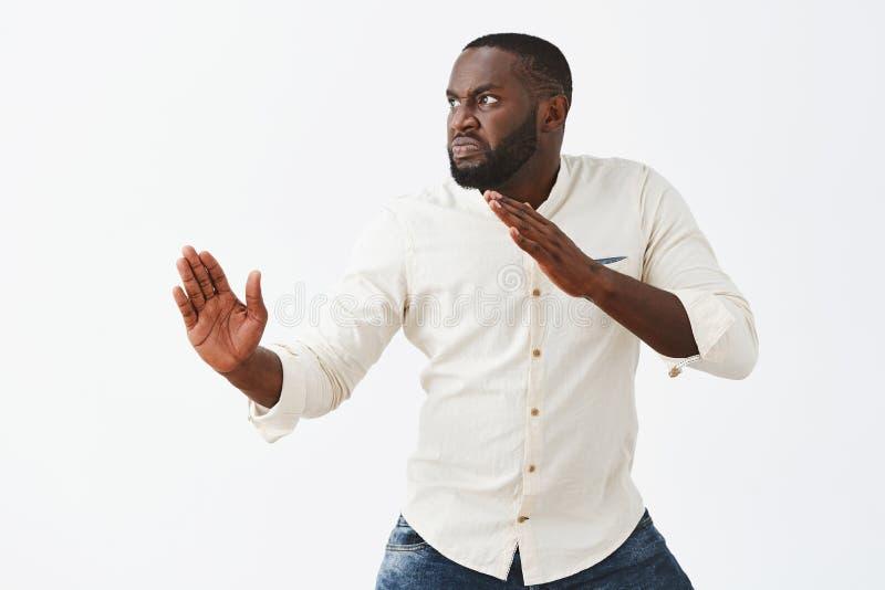 Śmieszny i figlarnie dorosły amerykanina afrykańskiego pochodzenia facet z brodą, stoi w profilu w sztuki samoobrony pozie z nast zdjęcie royalty free