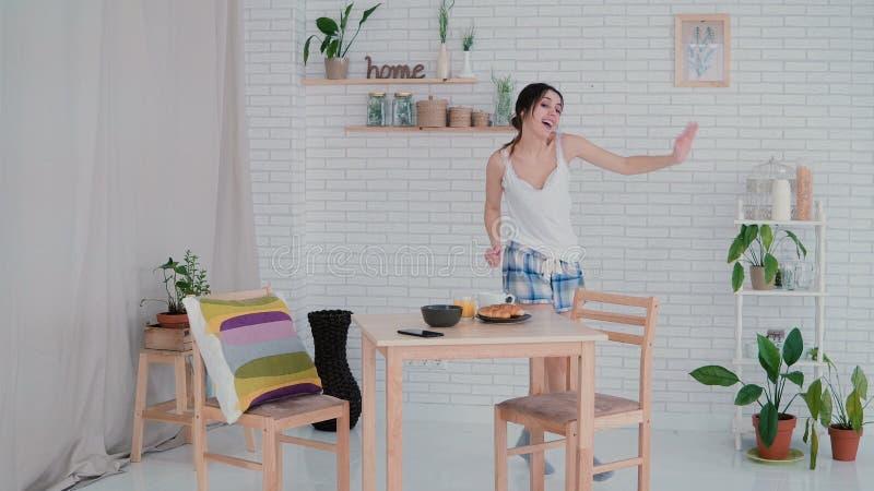 Śmieszny młoda kobieta taniec w kuchni jest ubranym piżamy w ranku Brunetki dziewczyna w rozochoconym nastroju słucha muzykę zdjęcia royalty free