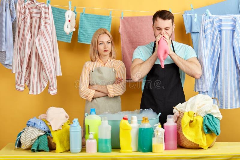 Śmieszny młody człowiek dmucha rękawiczka podczas gdy blondynki kobieta stoi blisko on fotografia stock