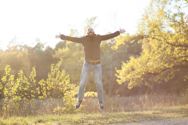 Śmieszny młody człowiek skacze up z brodą fotografia royalty free