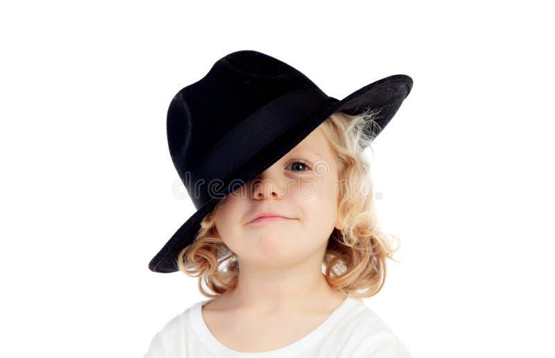 Śmieszny mały blond dziecko z czarnym kapeluszem obraz stock