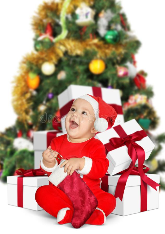 Śmieszny Mały dziecko Święty Mikołaj z Bożenarodzeniowymi prezentami na bielu obrazy stock