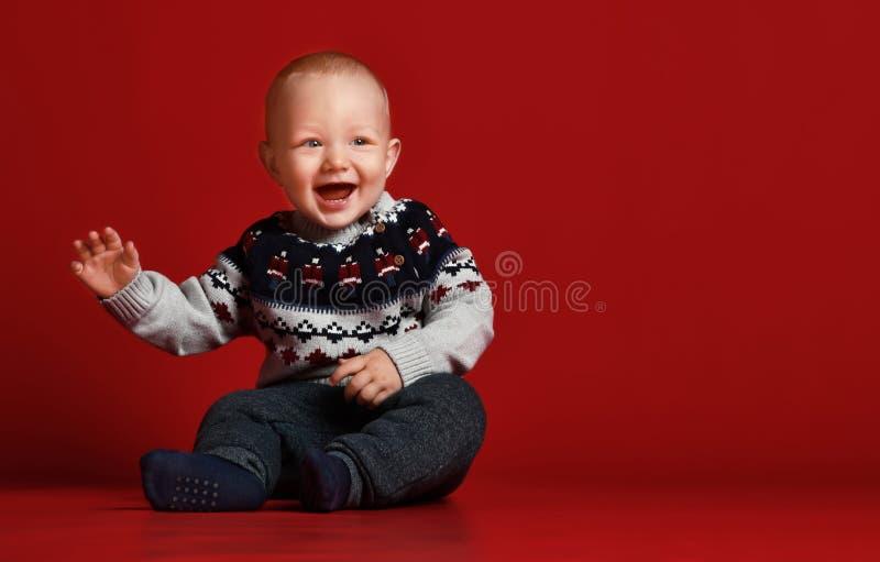 Śmieszny mały dziecko jest ubranym ciepłego trykotowego Bożenarodzeniowego pulower przy studiiem na zimnym zima dniu obraz stock