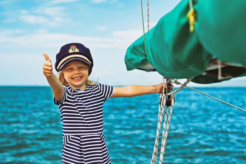 Śmieszny mały dziecko kapitan na pokładzie żeglowanie jachtu obraz royalty free
