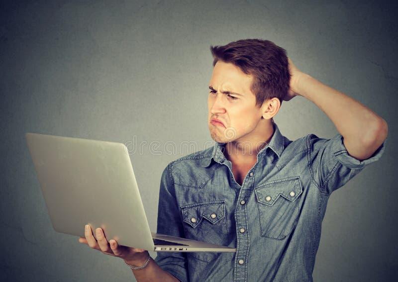 Śmieszny nieświadomy facet ma kłopoty z laptopem Skomplikowana technologia obraz stock