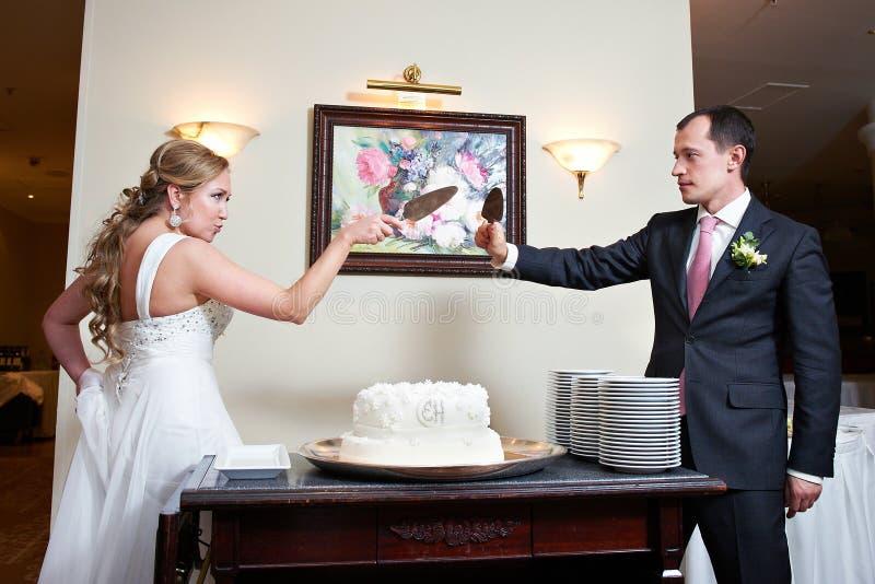 Śmieszny państwo młodzi blisko ślubnego torta fotografia royalty free