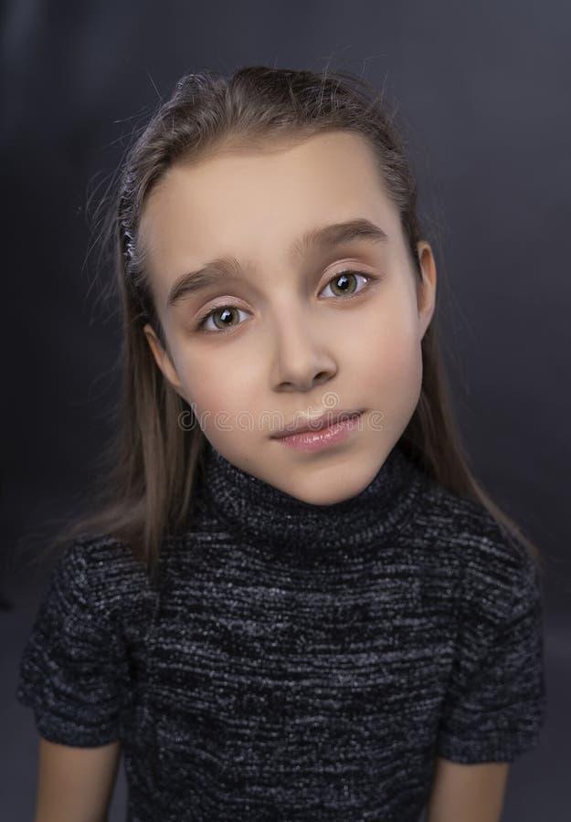 Śmieszny portret śliczna uśmiechnięta nastoletnia dziewczyna jest ubranym ciemnego turtleneck Szary t?o Reklamuje, modny i handlo zdjęcia royalty free