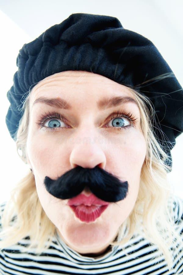 Śmieszny portret blond kobieta jako francuski mężczyzna z beretem i musta fotografia royalty free