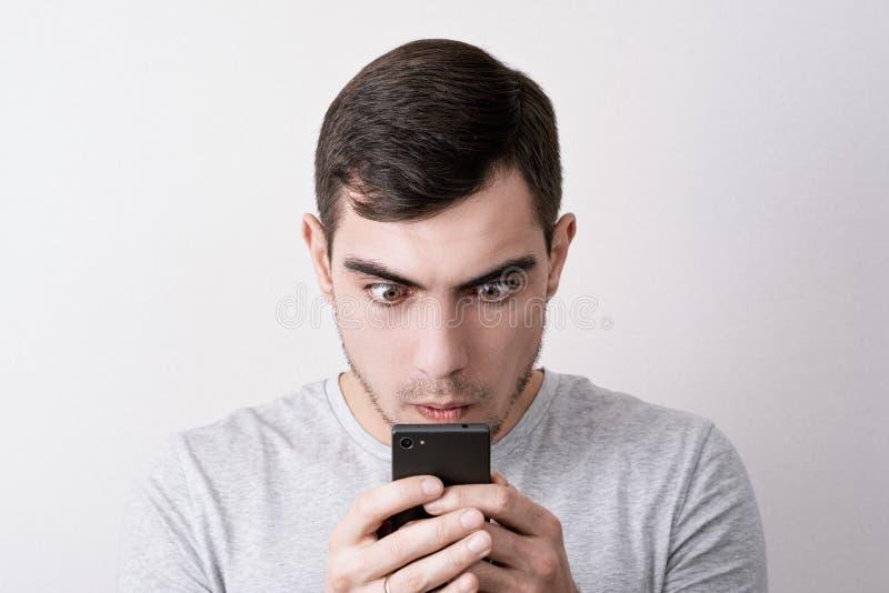 Śmieszny portret mężczyzna z smartphone w jego wręcza patrzeć ekran z wybrzuszać oczy zdjęcia stock