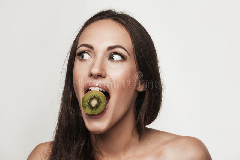 Śmieszny portret młodej kobiety mienia kiwifruit obrazy stock