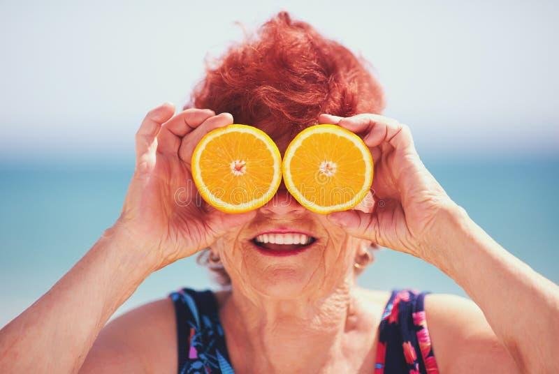 Śmieszny portret szczęśliwa dojrzała kobieta, babcia ma zabawę z pomarańcze ono przygląda się na wakacje aktywny tryb życia zdjęcie royalty free