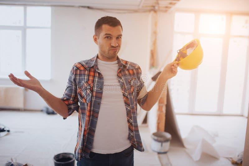 Śmieszny pracownik z budowa hełmem stoi na cbuilding miejscu i no zna czego robić obrazy stock