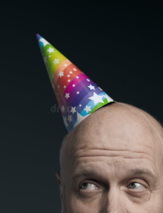 Śmieszny starszy łysy mężczyzna z partyjnym kapeluszem fotografia royalty free