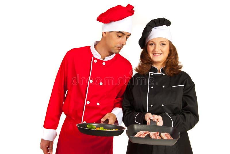 Śmieszny szef kuchni patrzeje w kolega nieckę fotografia royalty free