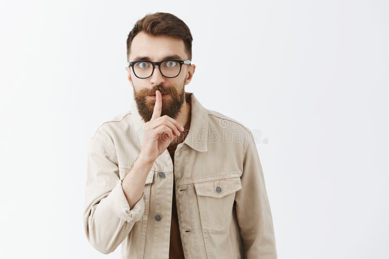 Śmieszny tajemniczy i wzmacniający elegancki brodaty facet garbi się mówić z strzelającymi oczami z szkłami w beżowej kurtce shh  obraz stock