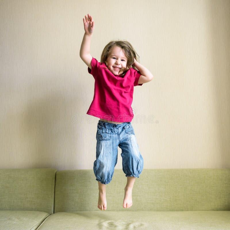 Śmieszny trzyletni dziecko skacze na leżance obrazy stock