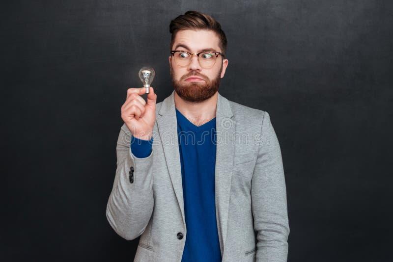 Śmieszny zadziwiający młody biznesmen trzyma małą żarówkę w szkłach fotografia royalty free