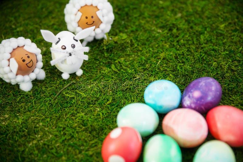 Śmieszny zwierzę kształtować postacie i kolorowi Easter jajka na zielonych półdupkach zdjęcie stock