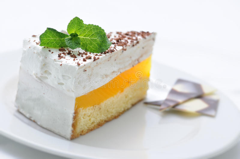Śmietanka tort na bielu talerzu, słodkim deserze i czekolady dekoraci z nowym liściem, patisserie, słodki deser, linii sklepowa f obraz stock
