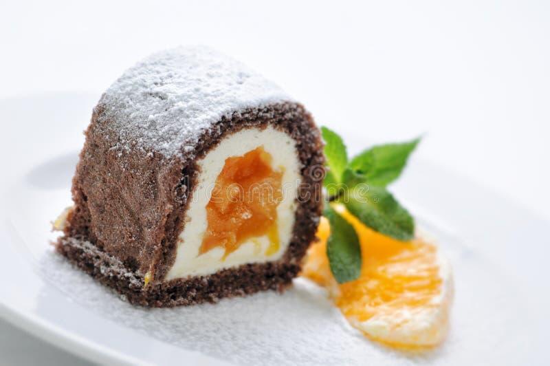 Śmietanka tort z pomarańczowym dżemem wewnątrz na bielu talerzu, produkt fotografii dla patisserie lub sklepie, obraz royalty free