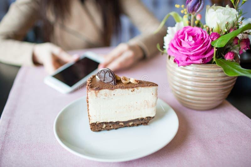 Śmietankowy cheesecake z czekoladowymi ciastkami i kremowymi ciastkami Oreo tort i piękna waza z kwiatami na stole Piękny fotografia royalty free