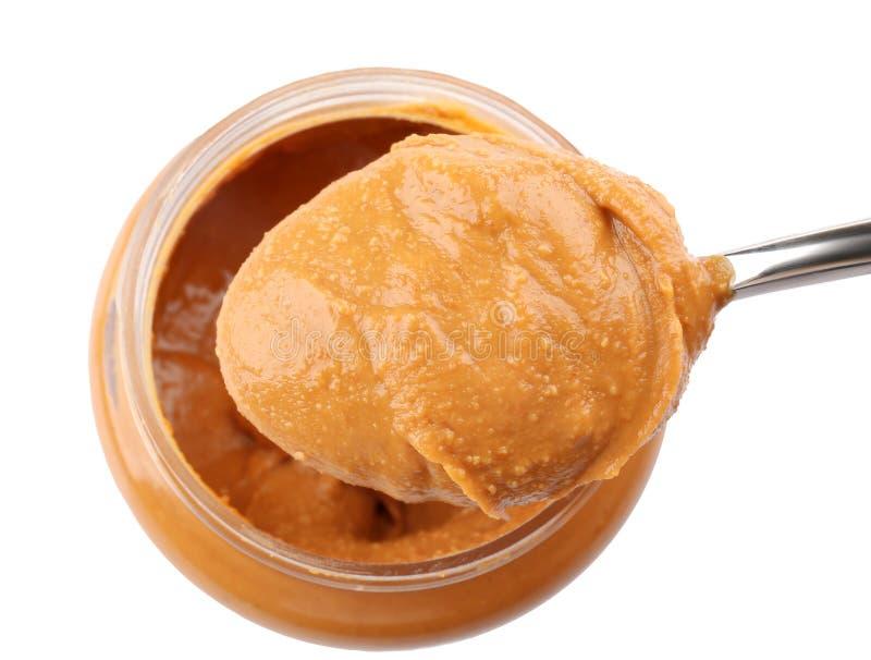Śmietankowy masło orzechowe w łyżce i słoju zdjęcia stock