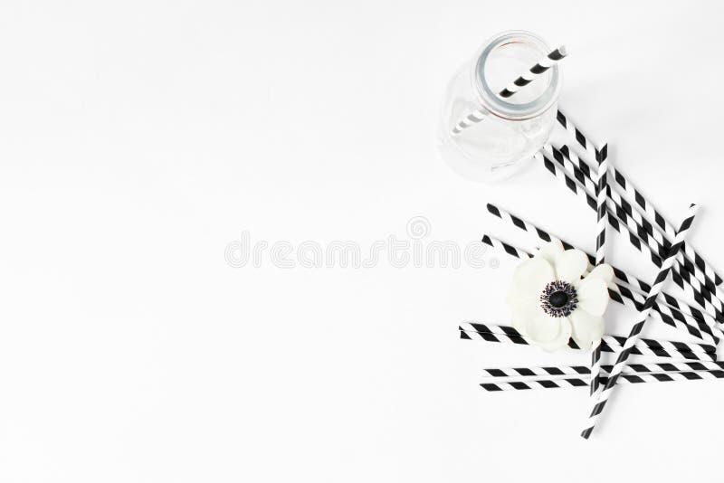 Śniadania lub przyjęcia urodzinowego desktop scena Skład z pustym dojnego szkła słojem, czarny i biały pije papierowe słoma zdjęcia stock