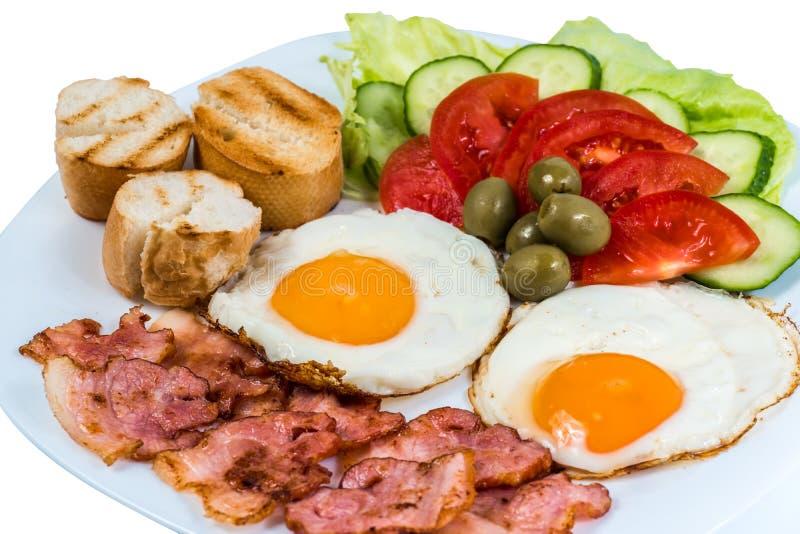 Śniadania smażący jajeczni świezi warzywa smażyli bekon i oliwki na białym talerzu zdjęcia stock