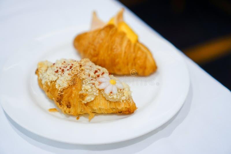 Śniadanie Świeży croissant z baleronem, serem i dżemem na bielu talerzu, fotografia royalty free