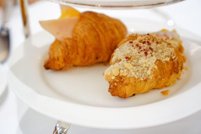 Śniadanie Świeży croissant z baleronem, serem i dżemem na bielu talerzu, zdjęcia royalty free