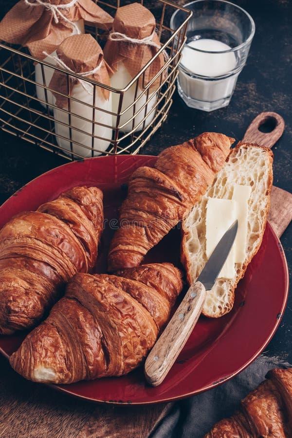 Śniadanie, świezi croissants z mlekiem na ciemnym tle Selekcyjna ostrość obraz royalty free