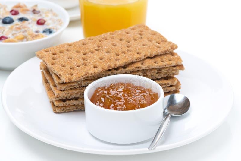 Śniadanie - chrupiący chleb z dżemem, sokiem pomarańczowym i muesli, fotografia royalty free