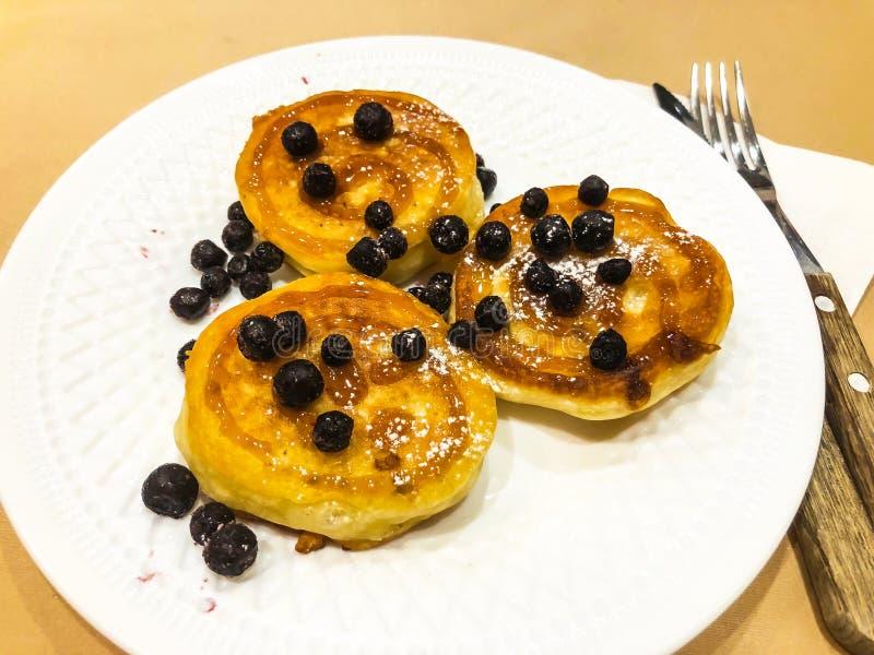 Śniadanie dla dziecka Wyśmienicie słodcy bliny z syropem, czarne jagody fotografia royalty free