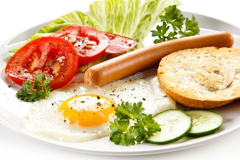 Śniadanie jajko, kiełbasa i warzywa - smażący, fotografia royalty free