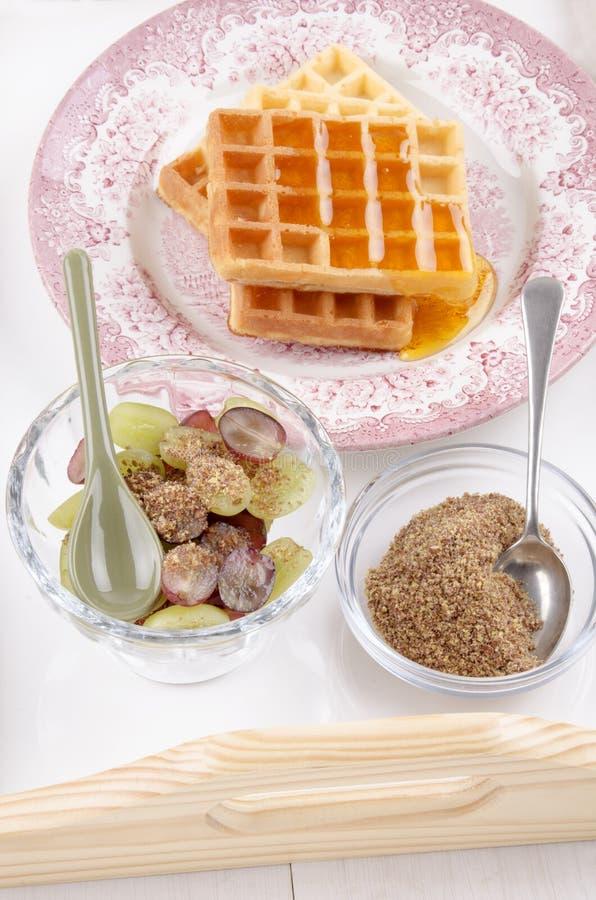 Śniadanie na porci tacy z winogronem, gofrem i mlejącym flaxse, fotografia stock