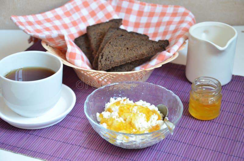 Śniadanie na stołowej filiżance z herbatą, chleb, twarogowy pomarańczowy dżem na purpurowej pielusze zdjęcie royalty free
