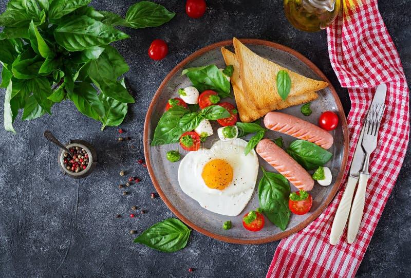 Śniadanie na walentynki ` s dniu - smażący jajka w kształta sercu, kiełbasie, grzance i caprese sałatce, zdjęcie royalty free