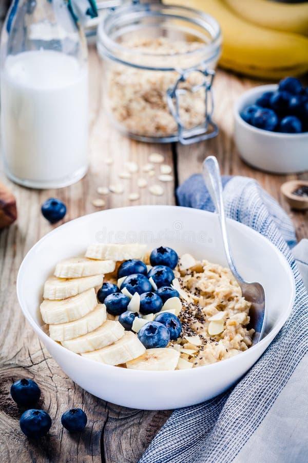 Śniadanie: oatmeal z bananami, czarnymi jagodami, chia ziarnami i migdałami, obrazy royalty free