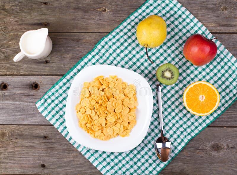 Śniadanie: płatki w talerzu, mleko w dzbanku fotografia stock