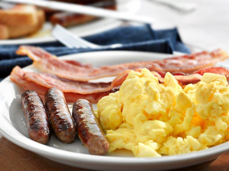 Śniadanie - rozdrapani jajka kiełbasa i bekon, obraz royalty free