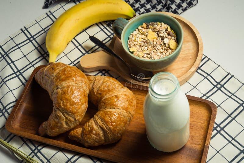 Śniadanie słuzyć z croissants, mlekiem, zbożem i bananem, obraz stock