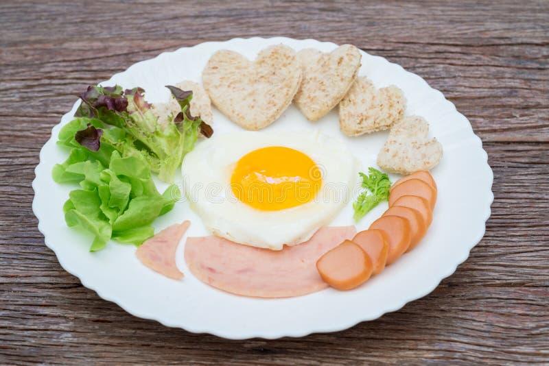 Śniadanie składa się smażącego jajko, baleron, kiełbasa, całej banatki chleb, świezi warzywa, stawiający talerze na starych drewn zdjęcia royalty free
