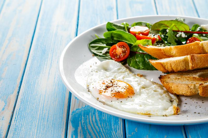 Śniadanie smażący jajko, grzanki i jarzynowa sałatka -, zdjęcie stock