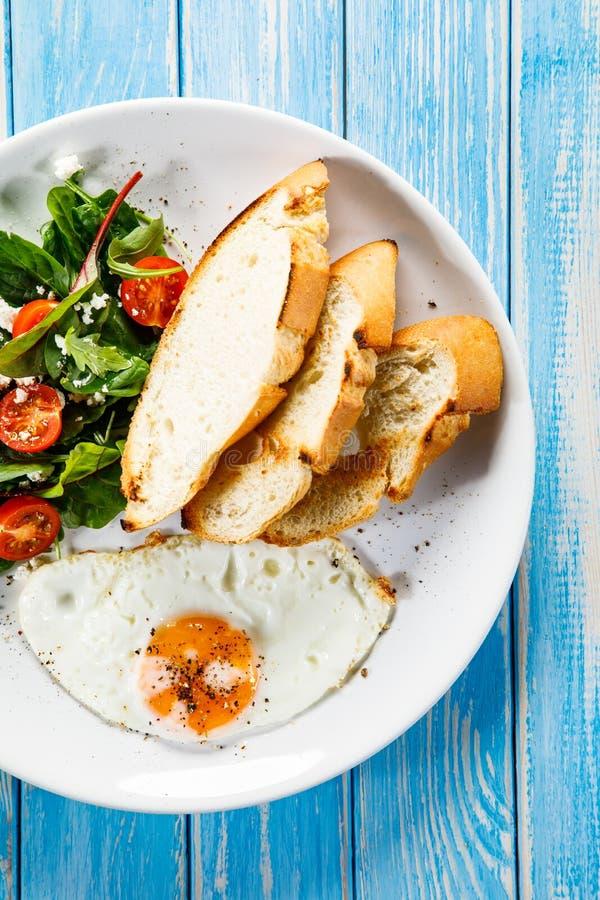 Śniadanie smażący jajko, grzanki i jarzynowa sałatka -, zdjęcia stock