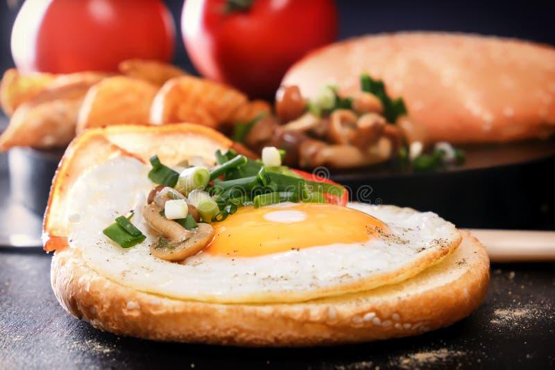 Śniadanie Smażący jajko na rolce, pomidor, zielenie, bekon, ono rozrasta się cutlery zbliżenie obraz stock